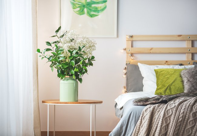 Bunch of flowers on small table next to bed in cozy bright bedroom